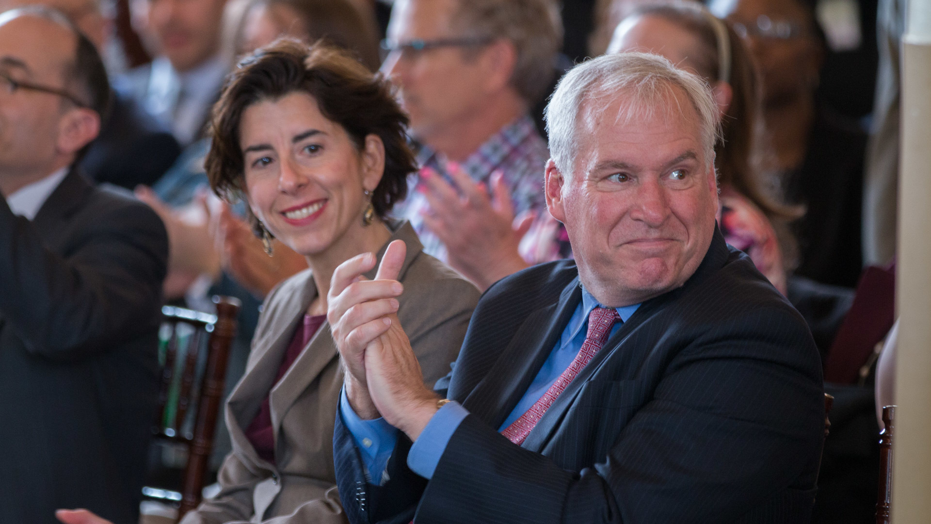 Photo of Eric S. Rosengren and Rhode Island Governor, Gina Raimondo clapping for the cities that won a multiyear grants in Rhode Island for the Working Cities Challenge Competition.