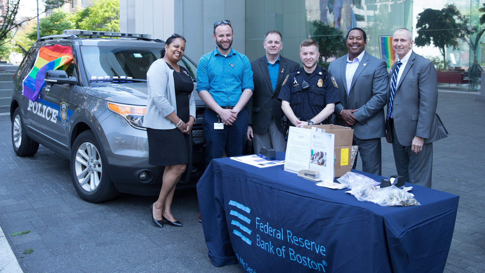 federal reserve bank of boston staff posing in front of the law enforcement cruiser with a pride flag long the side of it.